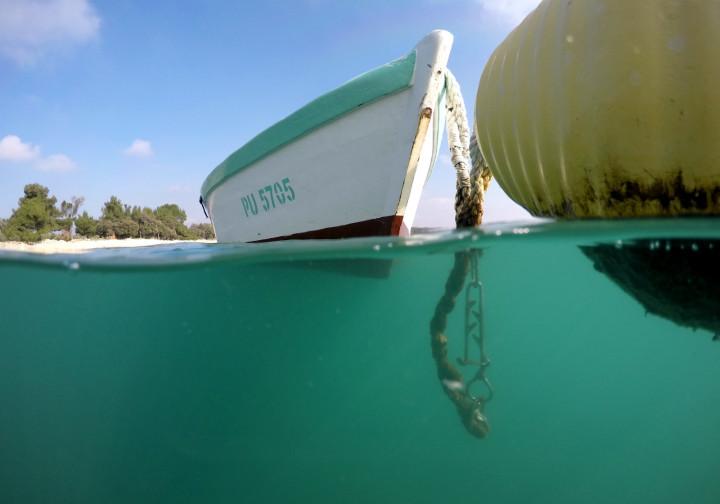 Half half photo of a boat and a buoy